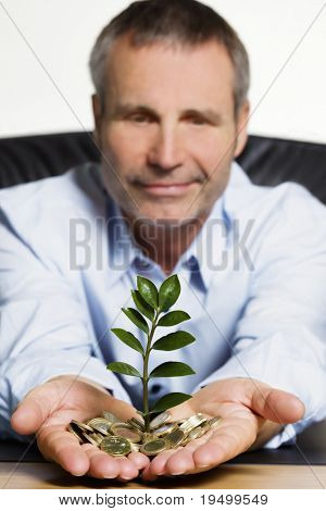 Happy confident senior businessman sitting at desk  presenting a green plant growing out of a pile of Euro coins symbolizing growth of financial wealth.
