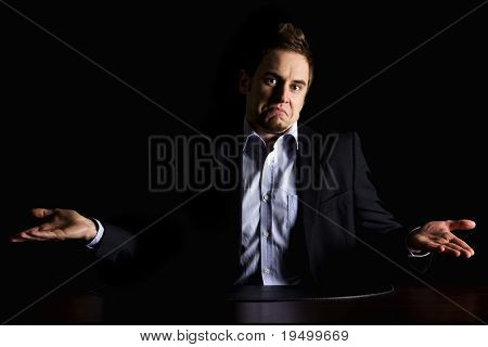 Low-key portrait of young clueless businessman in dark suit sitting at office desk being confused, isolated on black background with copy-space.
