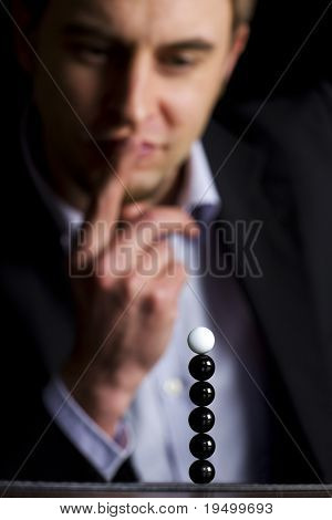 "Business person in dark suit sitting at office desk and looking at stack of balls thinking about new business ventures, symbolizing ""everything is possible"", low-key image."