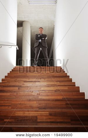 Confident smiling businessman in grey suit standing at top of office staircase looking down, symbolizing business success, achievement or successful career.
