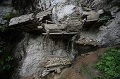 Groups of old family coffins with bones hanging on a rock. Tana Toraja region. Sulawesi island. Indo