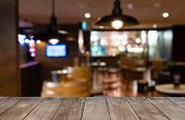 Empty Wooden Table In Front Of Blurred Background Of Tables And Bar Chairs poster