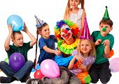 Birthday child clown playing with children . Kid wearing party hat hold balloons happiest birthday.  poster