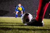 Low section of soccer player with ball against goalkeeper standing on playing field poster