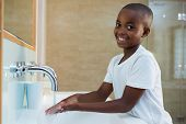 Portrait of smiling boy washing hands in sink at bathroom poster