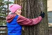 Woman Wearing Sportswear Hugging Tree poster