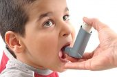 Close up image of a cute little boy ready to use inhaler for asthma from his mothers hand. White bac