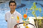 Waiter serving colorful cocktails by the pool.