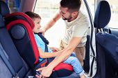 Side view of small handsome son in car seat being put in back of car by father poster