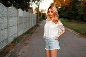 Beautiful Woman In Vintage T-shirt With Denim Shorts Outside The City On A Summer Day poster