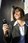Young female professional texting short message on mobile phone, focus on phone