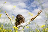 Young woman standing in yellow rapeseed field raising her arms expressing gratitude or freedom, view