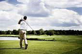 stock photo of golf  - Male golf player teeing off golf ball from tee box - JPG
