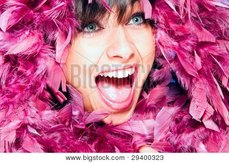 cheerful smiling woman in pink feather portrait, studio shot