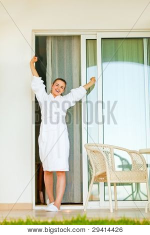 Happy Beautiful Female In Bathrobe Coming Out On On Terrace And