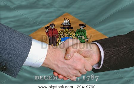 In Front Of American State Flag Of Delaware Two Businessmen Handshake After Good Deal