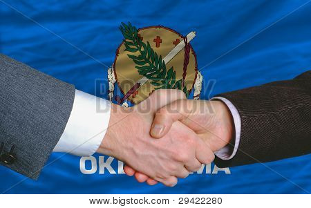 In Front Of American State Flag Of Oklahoma Two Businessmen Handshake After Good Deal