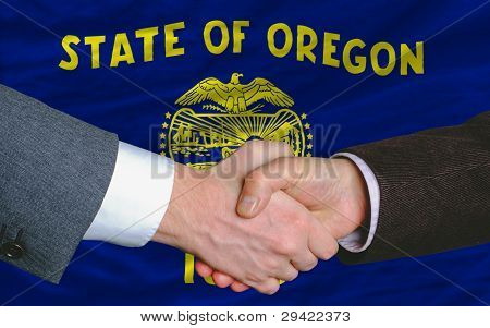 In Front Of American State Flag Of Oregon Two Businessmen Handshake After Good Deal