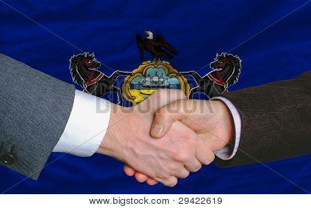 In Front Of American State Flag Of Pennsylvania Two Businessmen Handshake After Good Deal