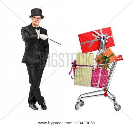 Full length portrait of a magician performing a trick on a shopping cart full of presents isolated on white background