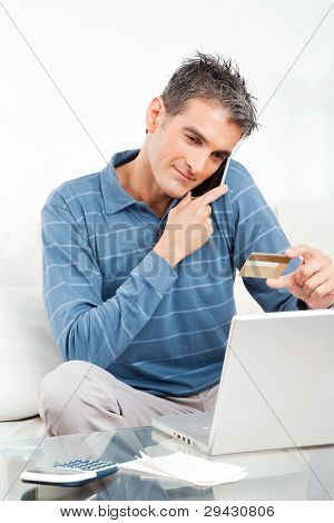Man shopping online with credit card and cell phone