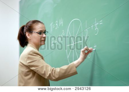 Young Teacher Writing On The Board