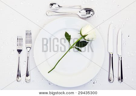 Photo of a table place setting with a white rose on the plate.