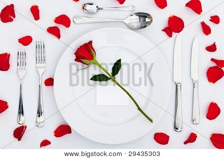 Photo of a table place setting with a red rose and blank card on the plate plus rose petals on the tablecloth. Add your own message to the place card.