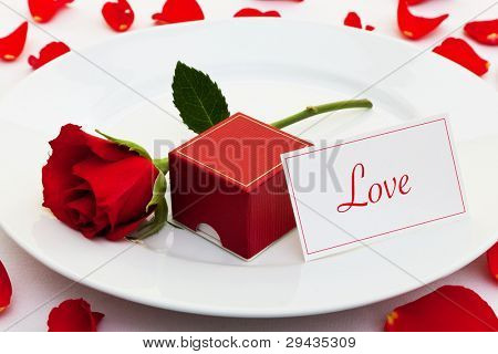 Photo of a red rose on a plate with a box for an engagement ring and a card with the word Love