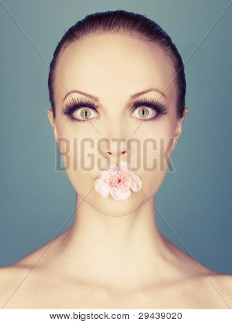 Portrait of beautiful young lady with flower in her mouth