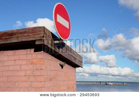 Road Sign Brick On Building. Pier And Sea Distance