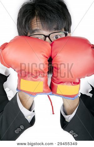 Scared Businessman Protecting His Face With Boxing Gloves