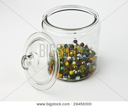 Glass Jar Half Full Of Colorful Glass Marbles