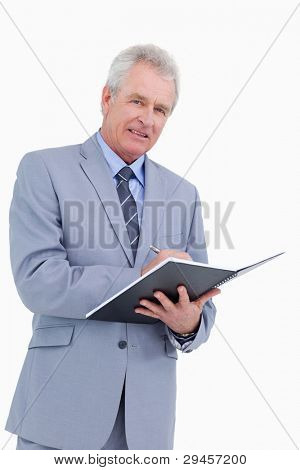 Smiling mature tradesman with pen and notebook against a white background