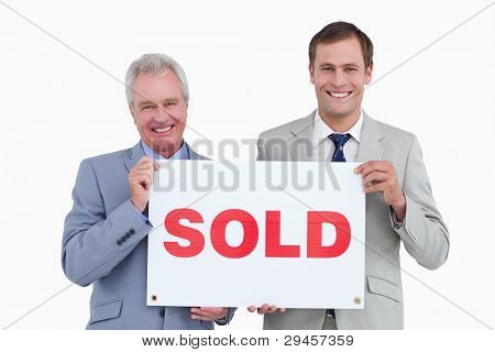 Smiling real estate agents holding sold sign against a white background