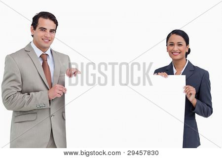 Smiling sales team holding blank sign against a white background