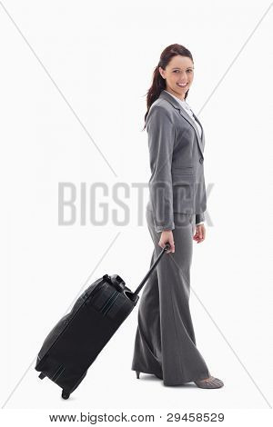 Profile of a businesswoman smiling with a suitcase against white background