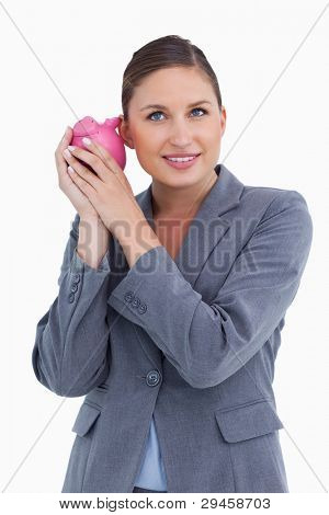 Smiling bank clerk shaking piggy bank against a white background