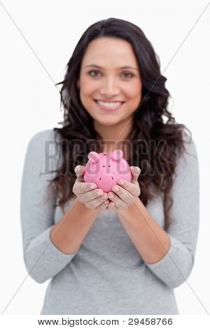 Piggy bank being held by smiling woman against a white background