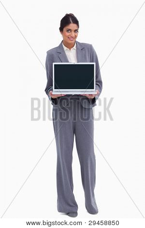 Smiling female entrepreneur presenting screen of her laptop against a white background