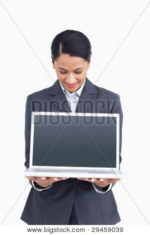 Close up of saleswoman presenting screen of her laptop against a white background