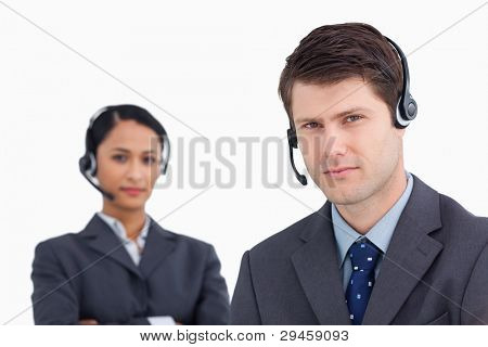Close up of serious looking call center agents against a white background