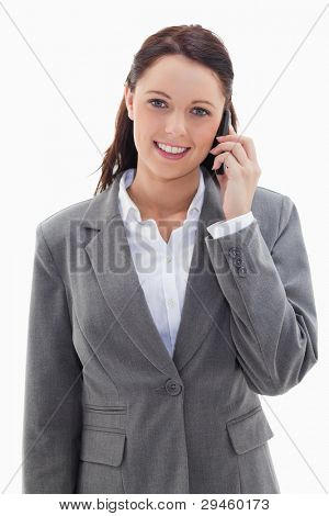 Businesswoman smiling over the phone against white background