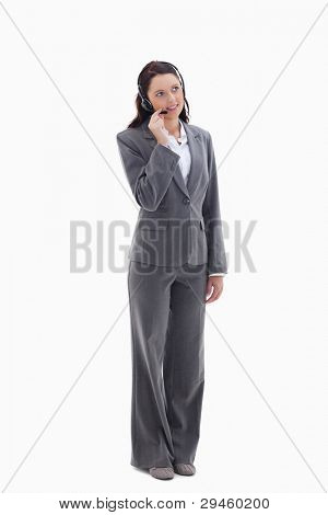 Businesswoman listening with a headset against white background