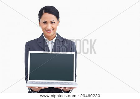 Close up of smiling saleswoman presenting laptop screen against a white background