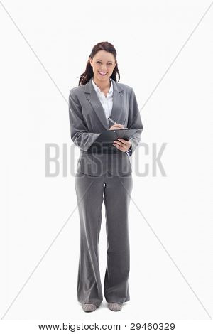 Businesswoman smiling while writing on a clipboard against white background