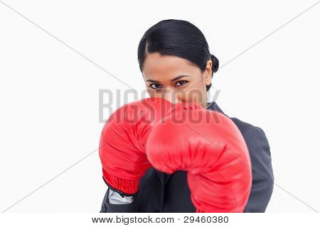 Close up of aggressive saleswoman with boxing gloves against a white background