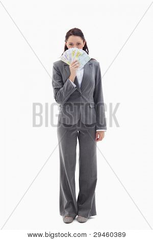 Businesswoman hiding with bank notes in her hand against white background