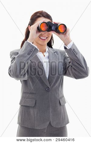 Close-up of a businesswoman smiling and looking through binoculars on the left side against white background