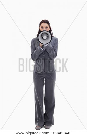 Expressive businesswoman speaking in a megaphone against white background